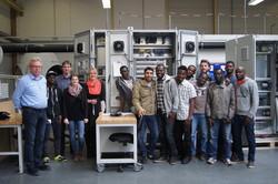 Ausbildungsleiter Holger Sumbeck von SSB Wind Systems (links) mit Organisatoren, Betreuern und Flüchtlingen während der Besichtigung der Produktion.