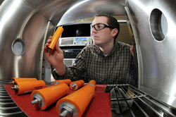 Researcher Lee Walker examines a lithium-ion battery cell (Photo via Argonne National Laboratory using a Creative Commons license).