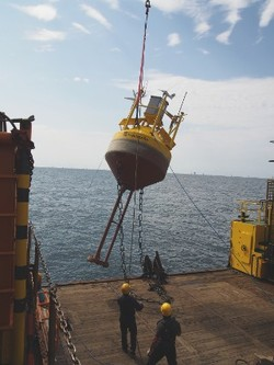 Deployment of the measuring buoy at an offshore site (© Photo Caspar Sessler)