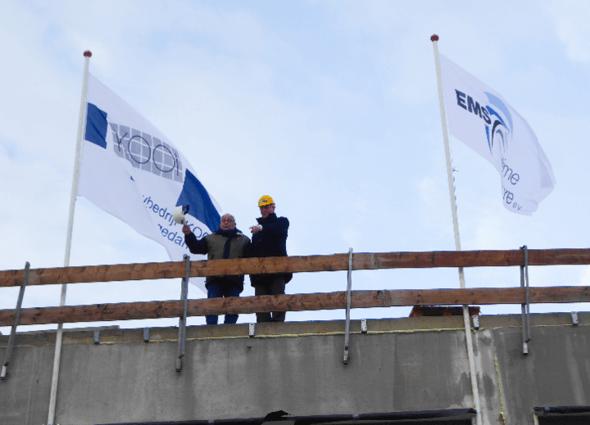 Enne Zweepe (li. Bauunternehmung KOOI) und Knut Gerdes (EMO BV) hissen die Unternehmensflaggen am höchsten Punkt des Gebäudes (Bild: EMO)