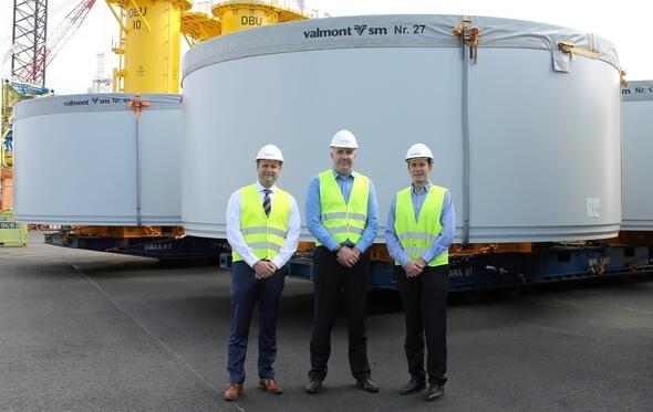 V.l.n.r.: Roland Schneider, Anders Engelhardt, und Marcus Braue in Cuxhaven, am Liegeplatz 4 vor den vor den auf Mafi-Trailern stehenden Windkraftkomponenten (Bild: HWG)