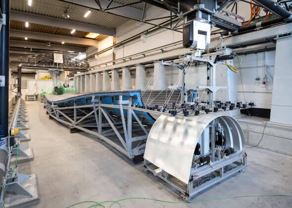 Vorgeschnittene Glasfasergelege werden zur Vorfertigung des Wurzeleinlegers automatisiert auf eine Positiv-Form abgelegt (Bild: Jan Meier)