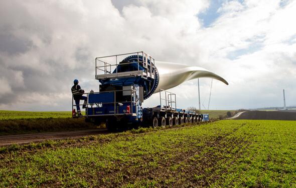 Das Foto zeigt den Transport eines knapp 60 Meter langen Rotorblatts zum Standort Imsweiler im rheinland-pfälzischen Donnersbergkreis (Bild: ABO Wind)