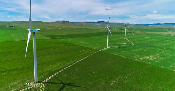 Four of the turbines on a TransAlta Renewables wind farm in Alberta, Canada, that were used for the wake-steering experiment. The truck in the lower left corner of the photo gives a sense of the wind turbines' size (Image: Calgary Drone Photography)
