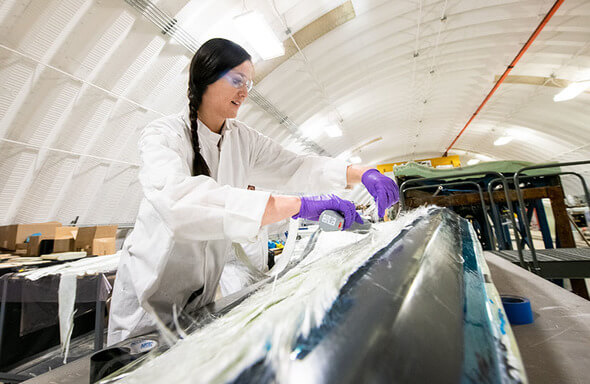 A woman works on the manufacture of a wind turbine blade. NREL researcher Robynne Murray works on a thermoplastic composite turbine blade at the Composites Manufacturing Education and Technology Facility at NREL's Flatirons Campus (Image: Dennis Schroeder