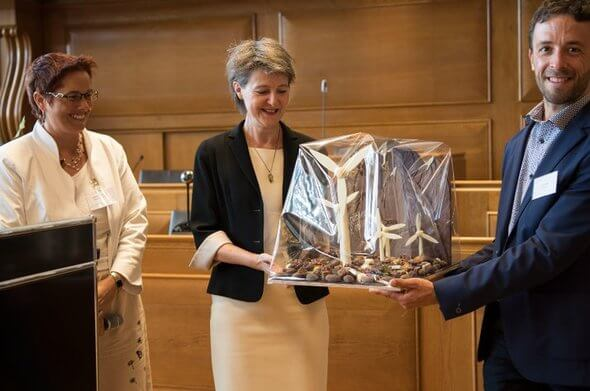 Isabelle Chevalley und Lionel Perret (beide Suisse Eole) übergeben Frau Bundesrätin Sommaruga einen Schoko-Windpark mit dem Schriftzug: 'Vergessen Sie die Windenergie nicht!' (Bild: P. Bosshard via Suisse Èole)