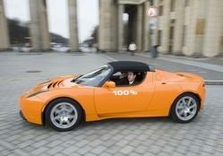 Willenbacher fährt im Elektro-Roadster Tesla vor dem Brandenburger Tor